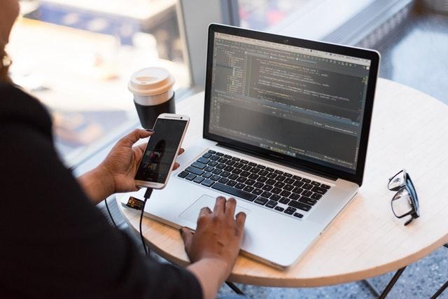 Persoon doet online boekhouding achter PC met smartphone